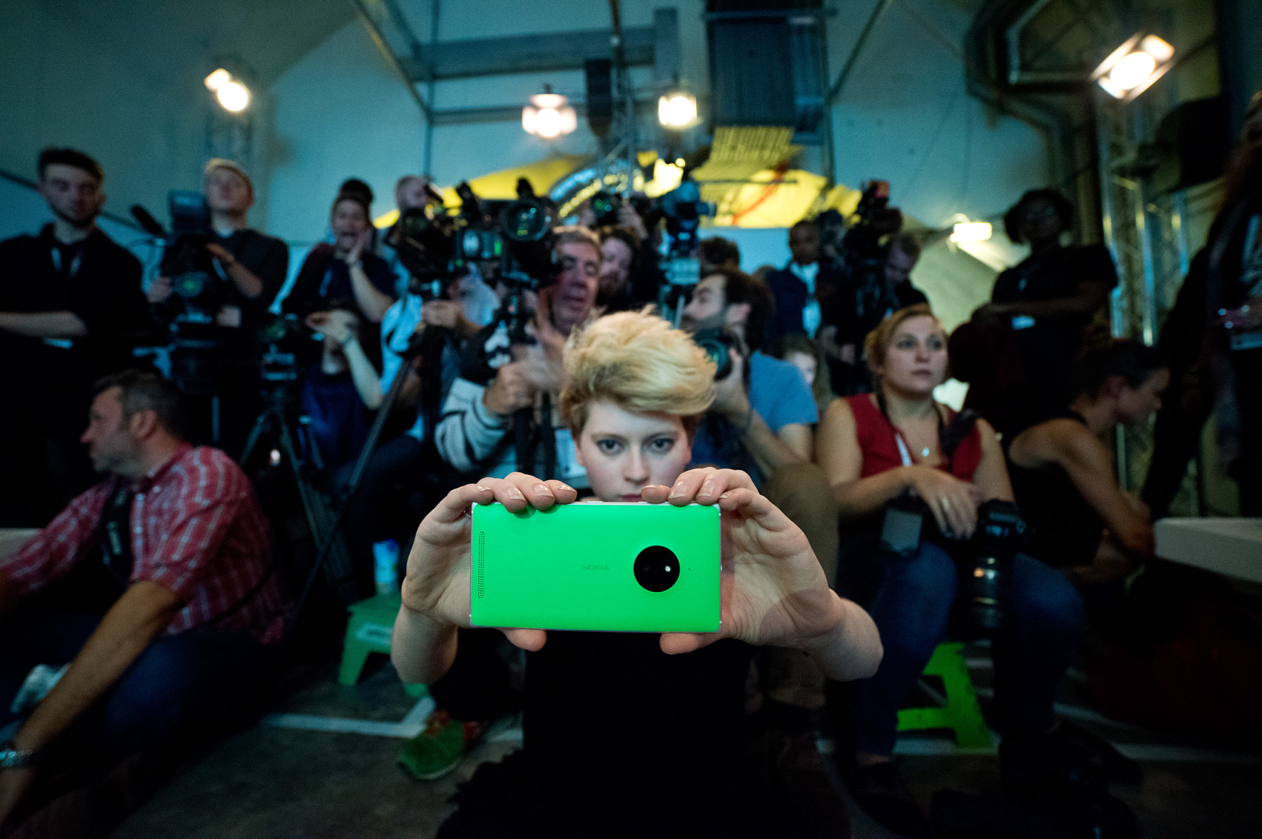 Girl holding smart phone in front of crowd at a fashion show, Fashion Innovation Agency