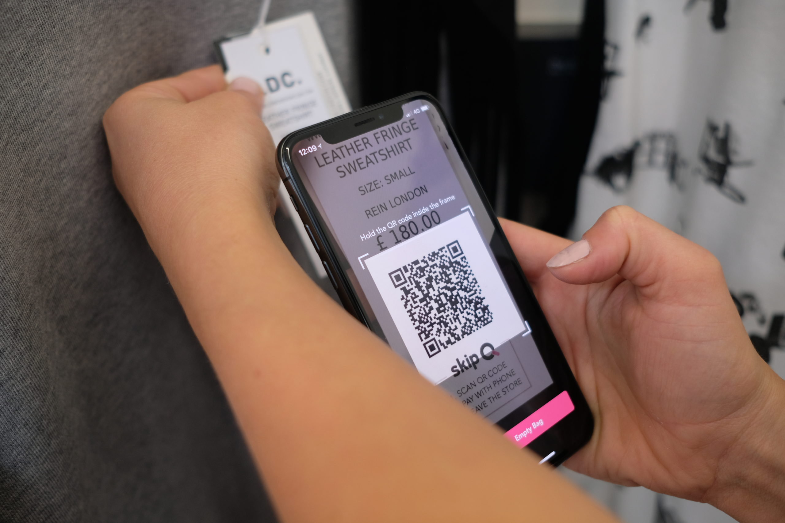 Mobile phone hovering over QR code on a clothing tag