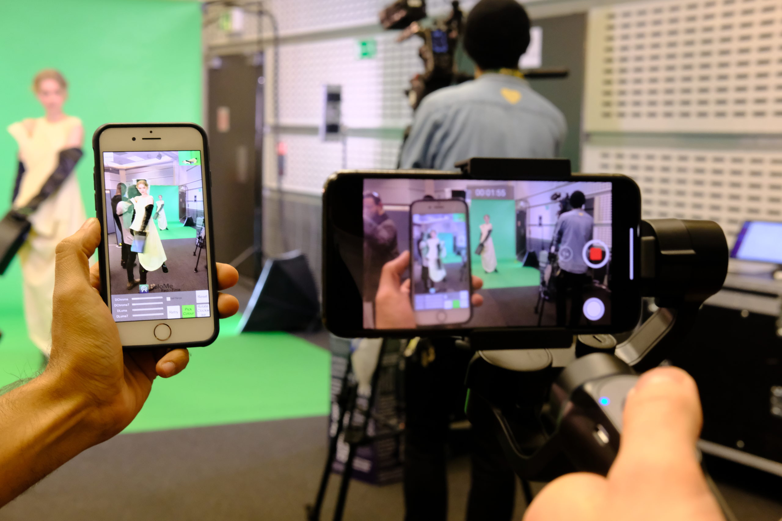 Image of phones taking pictures and video of a model on a green screen, Fashion Innovation Agency