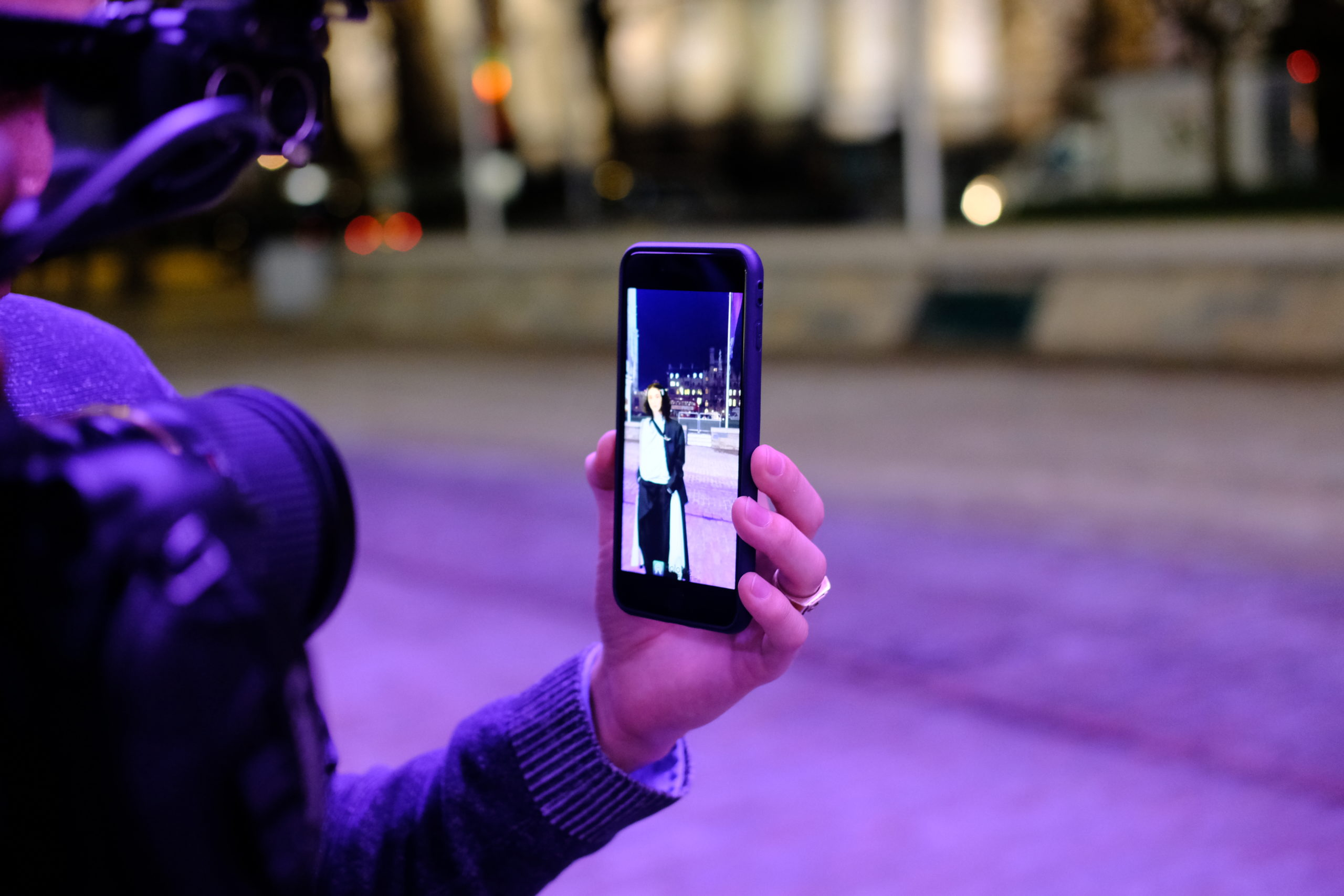 Person using phone to see augmented reality catwalk show, Fashion Innovation Agency